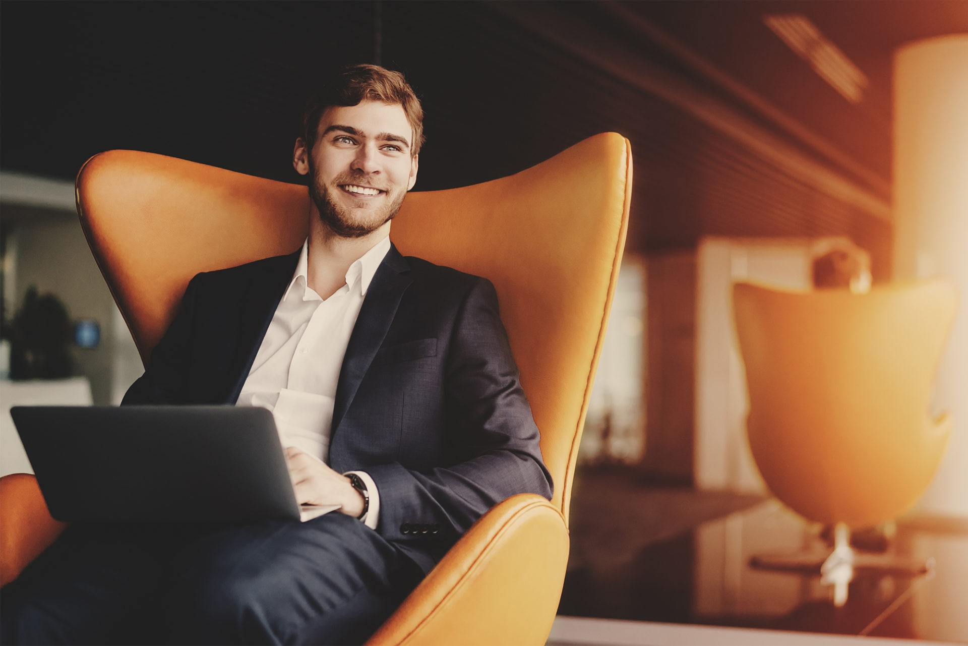 smiling young male professional sitting in chair with laptop