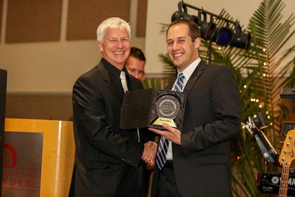 2013 entrepreneur of the year accepting award and posing with official